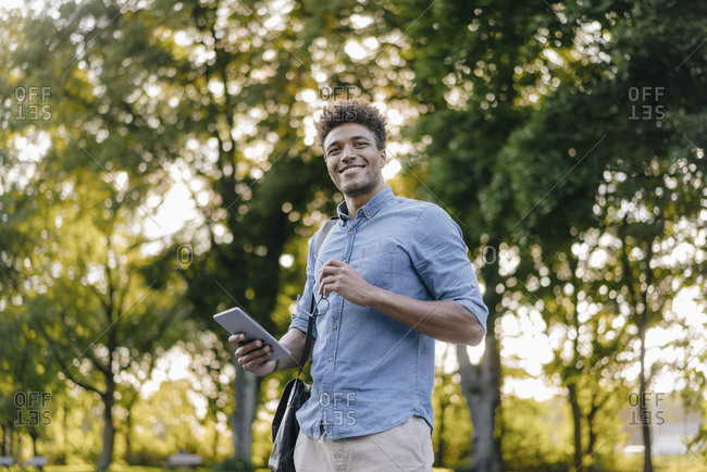Smiling young man holding cell phone in park