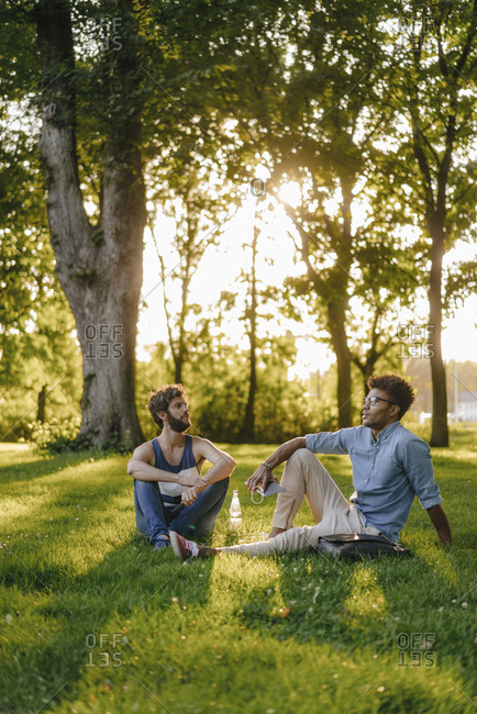 Two friends sitting in a park with mobile device and papers