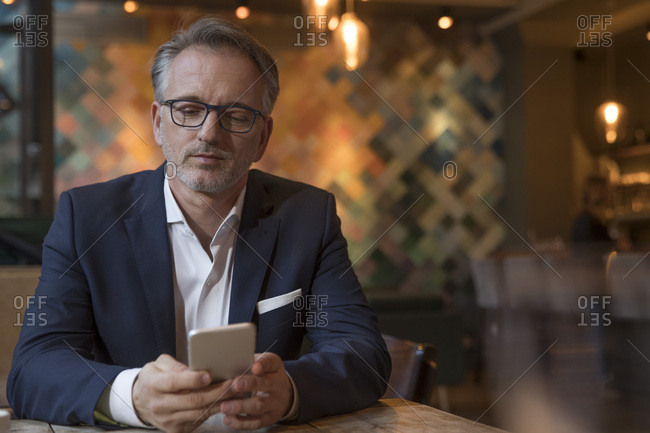 Portrait of businessman using smartphone in a restaurant