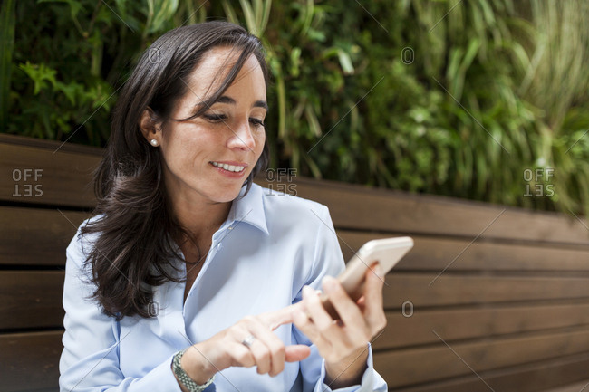 Smiling businesswoman using cell phone in garden cafe