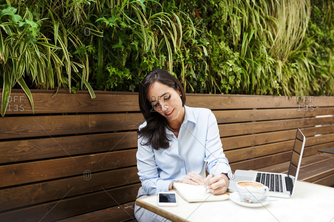 Busy businesswoman working at an outdoor cafe