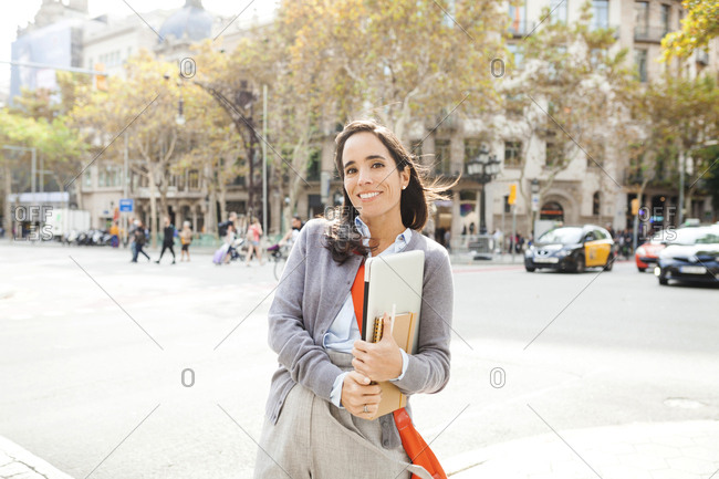 Portrait of smiling woman holding notebook in the city
