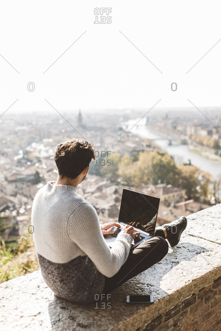 Italy- Verona- tourist using laptop- observation point