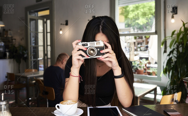 Brunette girl taking a picture with her film camera in a coffee shop