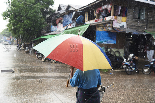 Myanmar- back view of man under umbrella in the rain
