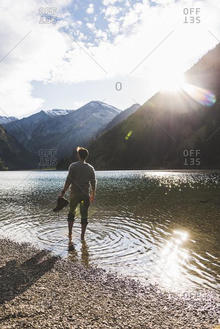 Austria- Tyrol- hiker refreshing in mountain lake