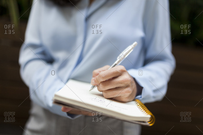 Close-up of businesswoman taking notes