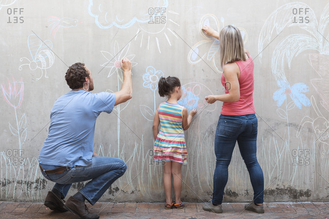 Family drawing colorful pictures with chalk on a concrete wall