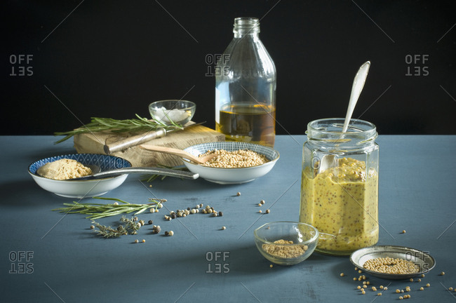 Homemade mustard in a glass with spoon- various ingredients
