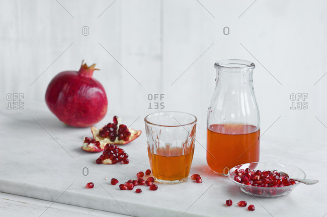Glass and bottle of pomegranate juice and whole pomegranate and pomegranate seed
