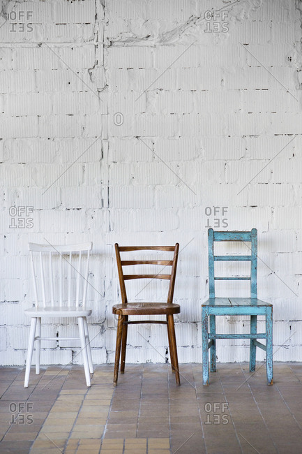 Empty chairs against white brick wall