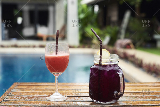 Two fruity cocktails at the poolside in rain