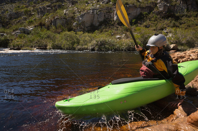 Woman kayaking in river on a sunny day