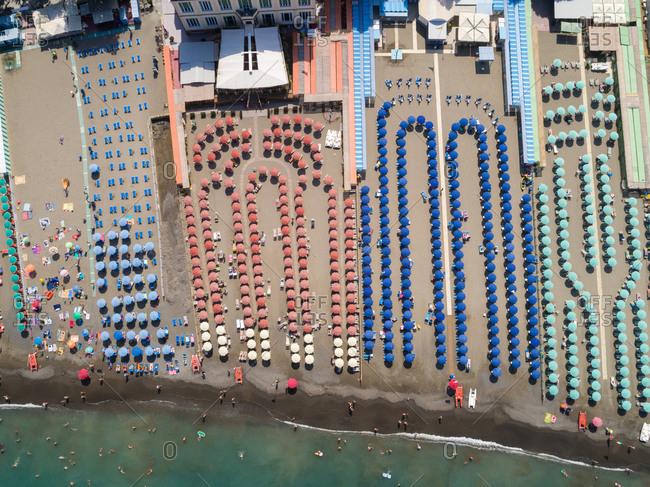 Aerial of Multi colored beach umbrellas at the coast