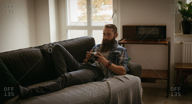 Man reviewing picture on digital camera while relaxing on sofa