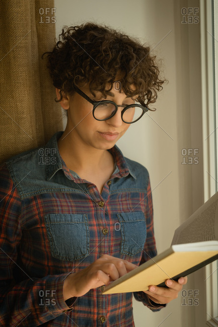 Close-up of woman reading book at home
