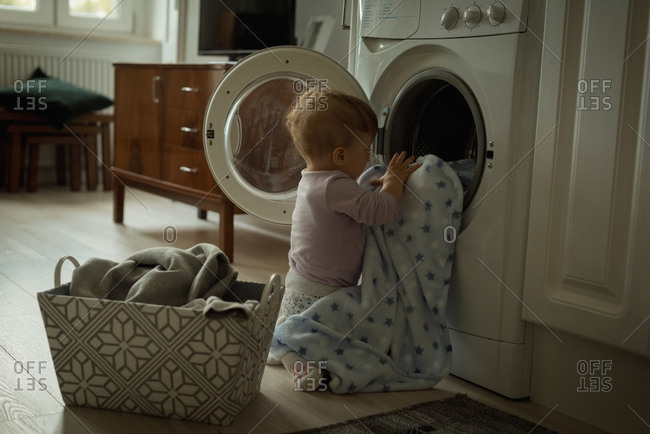 Baby putting clothes inside the washing machine at home