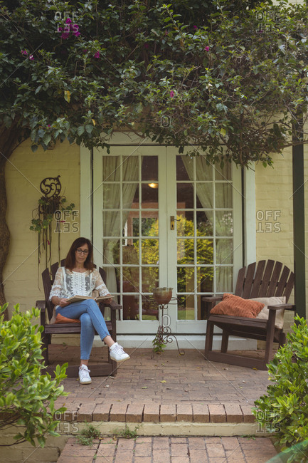 Woman reading book in porch