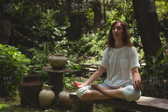 Woman practicing yoga in garden on a sunny day