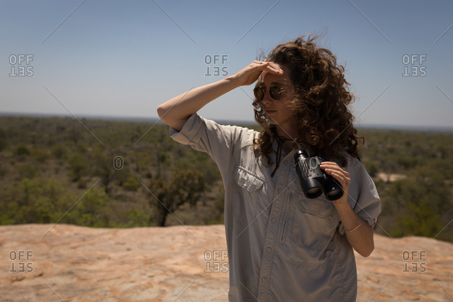 Beautiful woman shielding her eyes from sun in safari grassland