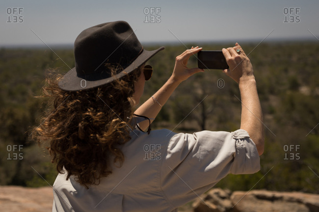 Woman taking picture with mobile phone on a sunny day