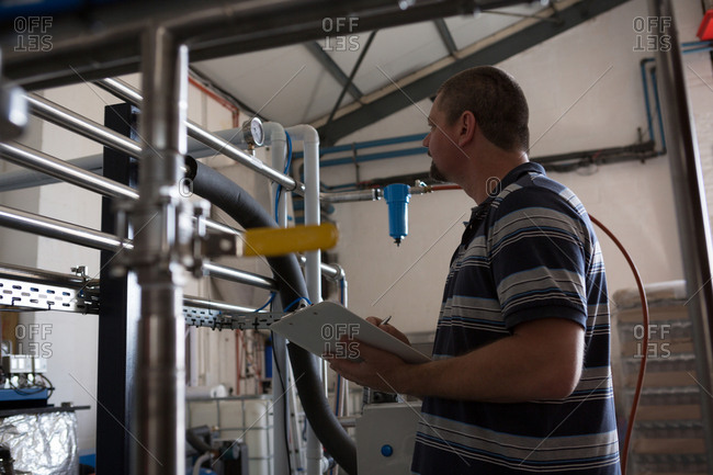 Male worker monitoring a pressure gauge of storage tank in gin factory