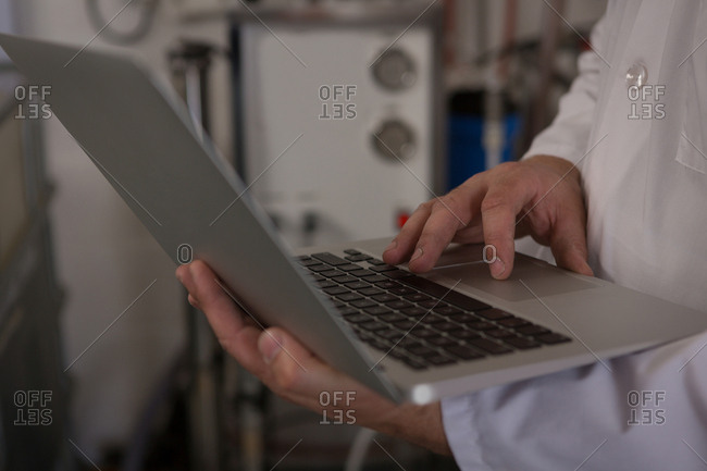 Mid section of worker using laptop in gin factory