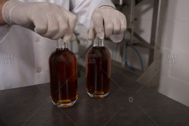 Mid section of worker holding gin in bottles at factory