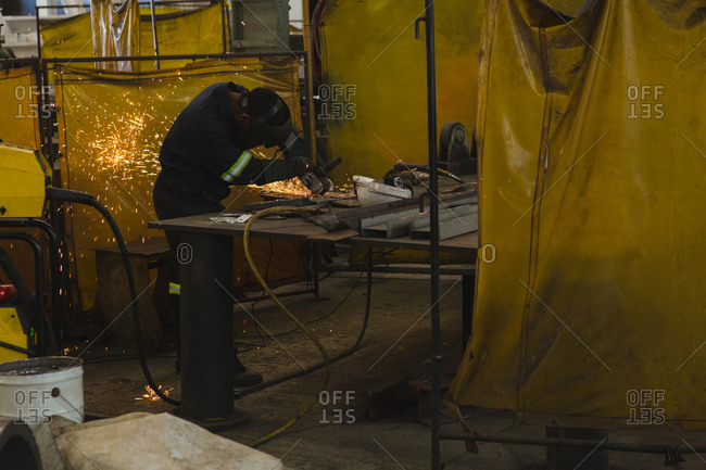 Welder repairing vessel part in workshop