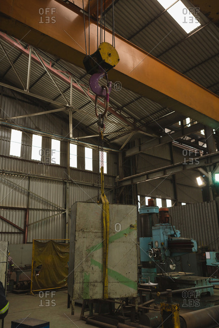 Metal hook lifting vessel part in workshop
