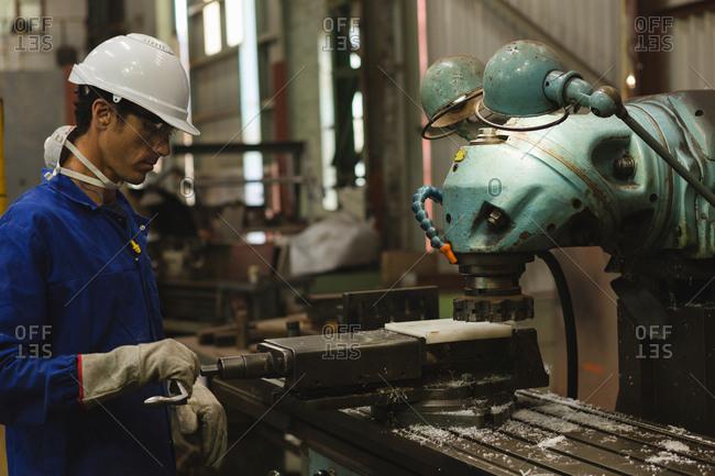 Worker using milling machine in workshop