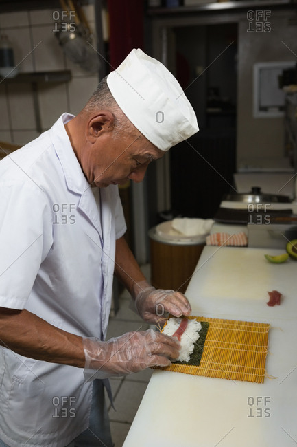 Senior chef preparing sushi in kitchen at hotel