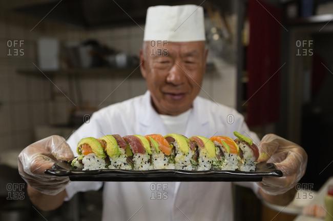 Senior chef holding tray of sushi in kitchen at hotel