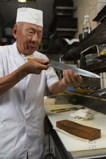 Senior chef holding knife in kitchen at hotel