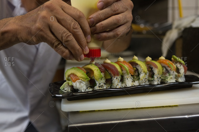Close-up of chef arranging sushi in a tray