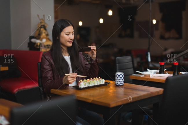 Woman taking photo of meal with mobile phone in restaurant
