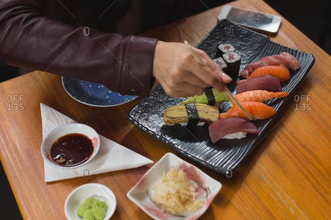 Close-up of woman having sushi food in restaurant