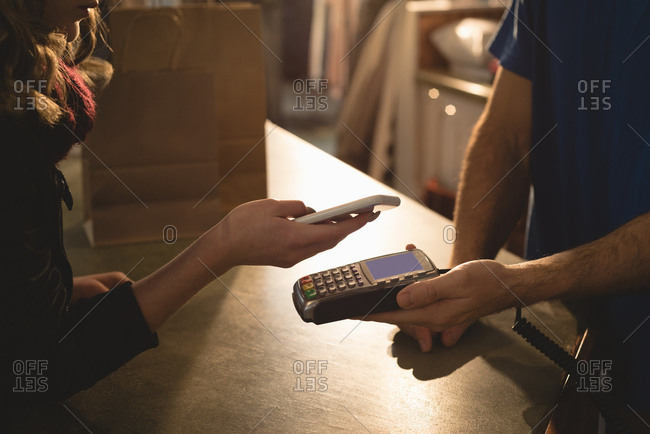 Woman making payment through mobile phone at counter
