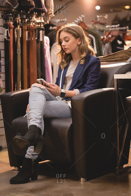 Beautiful woman using mobile phone on couch at shopping mall