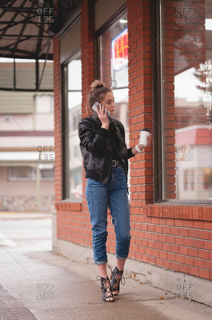 Beautiful woman talking on mobile phone while having coffee outside the mall