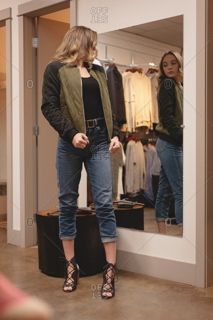Beautiful woman checking jacket in front of the mirror at shopping mall