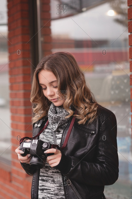 Close-up of beautiful woman reviewing picture on digital camera