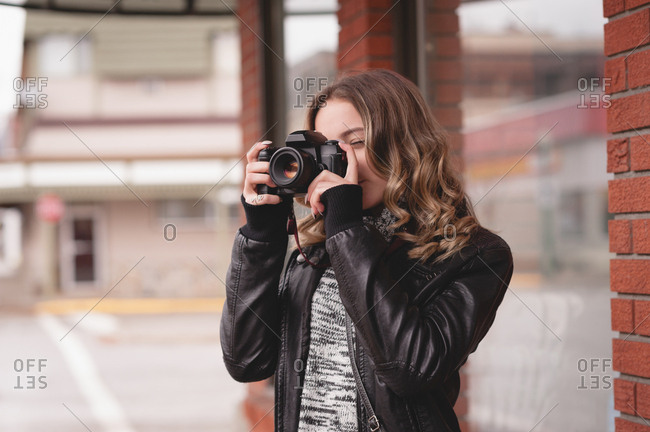 Attractive woman taking picture with digital camera