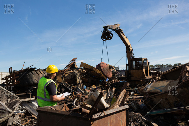 Rear view of worker monitoring the thrash being lifted by crane
