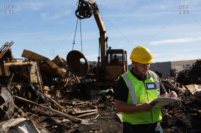 Concentrated worker writing on a clipboard in the scrapyard