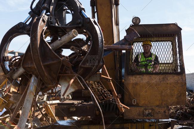 Close-up of crane lifting scrap metal in the junkyard
