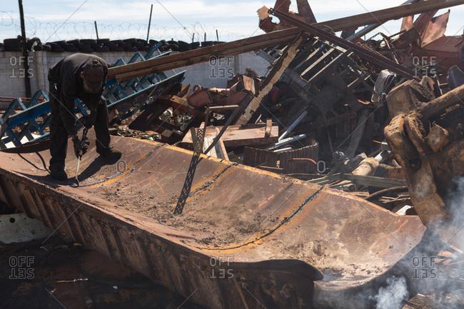 Worker working on metal scrap in scrapyard