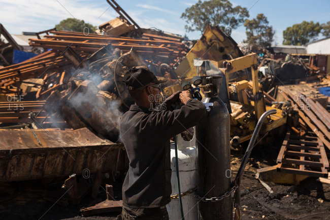 Worker closing the cylinder tap in scrapyard