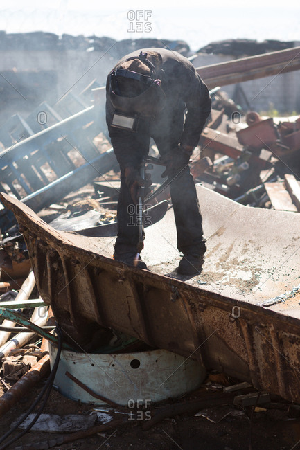 Rear view of worker cutting the metal in the scrapyard