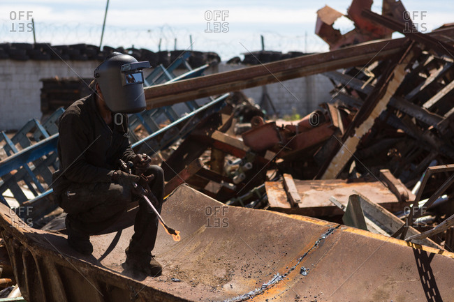 Worker cutting the metal in the scrapyard on a sunny day